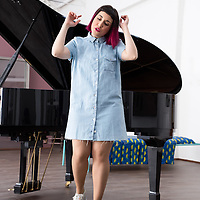Young female singer performing in front of a grand piano