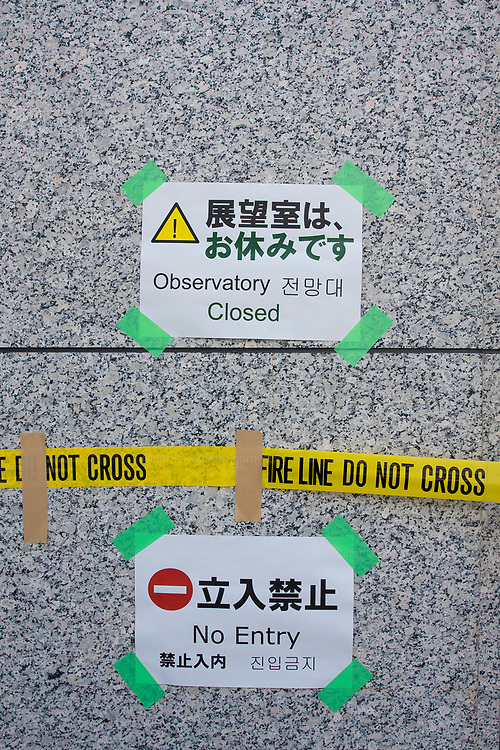 Signs on the Tokyo Metropolitan Government building informing visitors that  the 45th floor observation decks are closed after a magnitude 9 earthquake and large tsunami hit the Tohoku region of north east Japan  on March 11th killing nearly 20,000 people and causing massive destruction along the whole coast, and a melt-down at the Fukushima Daichi nuclear power station. Shinjuku,  Japan. Sunday March 13th 2011