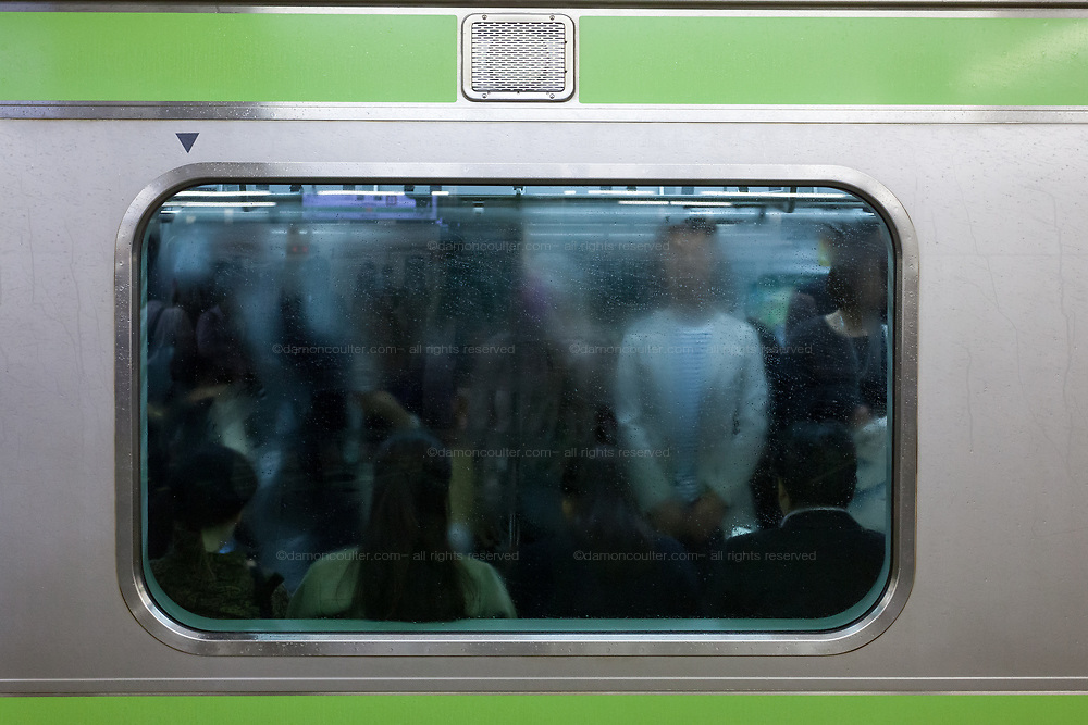 Commuters seen through a rain-splashed and misted-up window of a Yamanote Line train train Shinjuku Station, Tokyo, Japan. Friday October 6th 2017