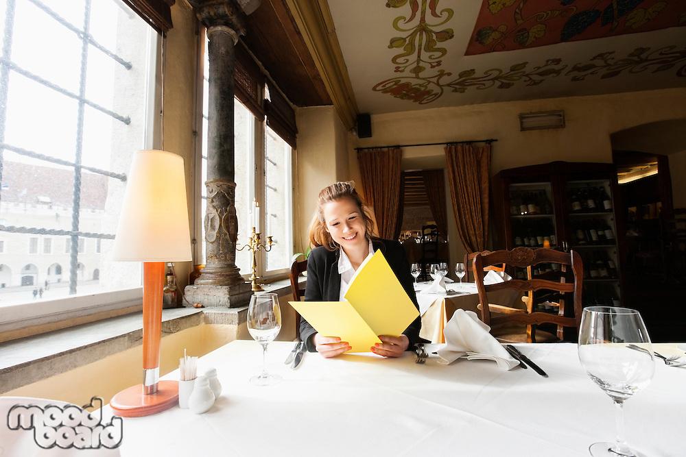 Smiling customer reading menu at restaurant table