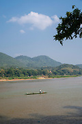 Image of a fisher preparing for the day along the Mekong River, Luang Prabang, Laos.