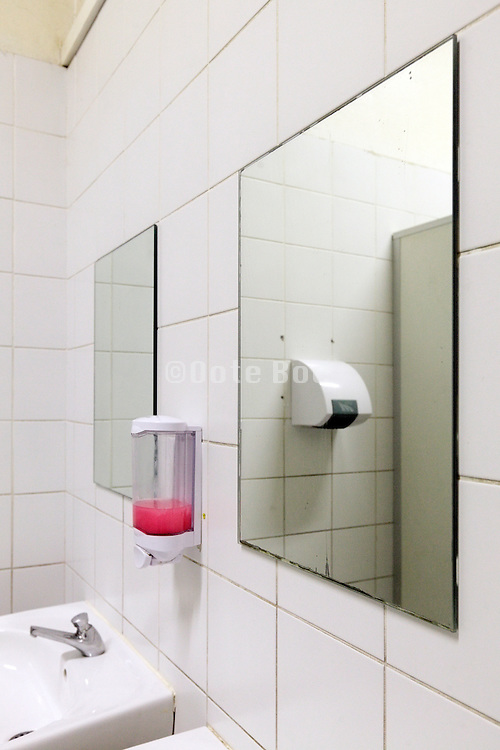 mirror sink and soap dispenser in a public bathroom