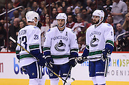 Nov 5, 2013; Glendale, AZ, USA; Vancouver Canucks forward Henrik Sedin (33) , defensemen Kevin Bieksa (3) and forward Ryan Kesler (17) talk on on the ice in the first period against the Phoenix Coyotes at Jobing.com Arena. The Coyotes defeated the Canucks 3-2 in an overtime shoot out. Mandatory Credit: Jennifer Stewart-USA TODAY Sports