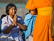 """02 JANUARY 2015 - KHLONG LUANG, PATHUM THANI, THAILAND: A woman prays at Wat Phra Dhammakaya as a monk walks past her at the start of the 4th annual Dhammachai Dhutanaga (a dhutanga is a """"wandering"""" and translated as pilgrimage). More than 1,100 monks are participating in a 450 kilometer (280 miles) long pilgrimage, which is going through six provinces in central Thailand. The purpose of the pilgrimage is to pay homage to the Buddha, preserve Buddhist culture, welcome the new year, and """"develop virtuous Buddhist youth leaders."""" Wat Phra Dhammakaya is the largest Buddhist temple in Thailand and the center of the Dhammakaya movement, a Buddhist sect founded in the 1970s.   PHOTO BY JACK KURTZ"""
