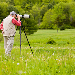 A man photographing wildlife in a field at Highland Farm in York, Maine.