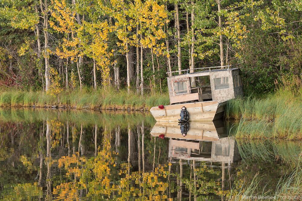 Old boat on the shore of Otto Lake, autumn, Healy, Alaska