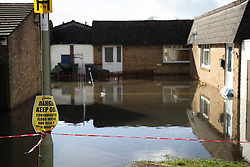 © Licensed to London News Pictures. 22/02/2014. Basingstoke, Hampshire. A 'DANGER KEEP OUT' sign warning people of contaminated flood water on Grampian Way, in the Buckskin area of Basingstoke, Hampshire. Groundwater levels are continuing to rise in the area, forcing 69 homes to be evacuated in the Buckskin Area of the commuter town. Photo credit : Rob Arnold/LNP