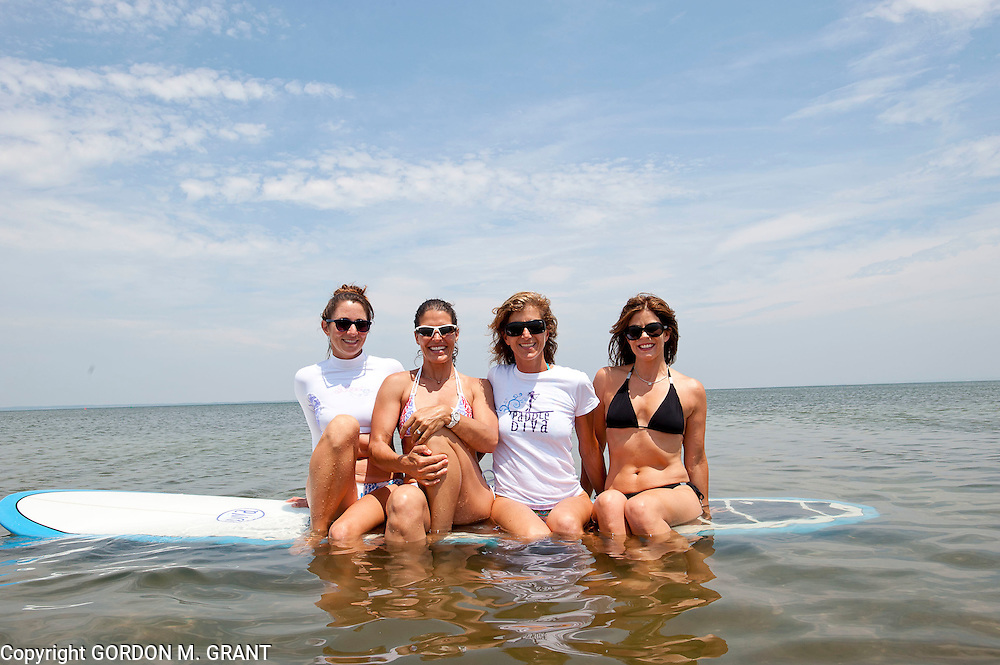 (l-r) Peri Allen, Jennifer Ford, Gina Bradley, the owner of Paddle Diva, and Meg Salen, take a break from a paddleboard lesson at Louse Point in East Hampton.  (June 24, 2010)