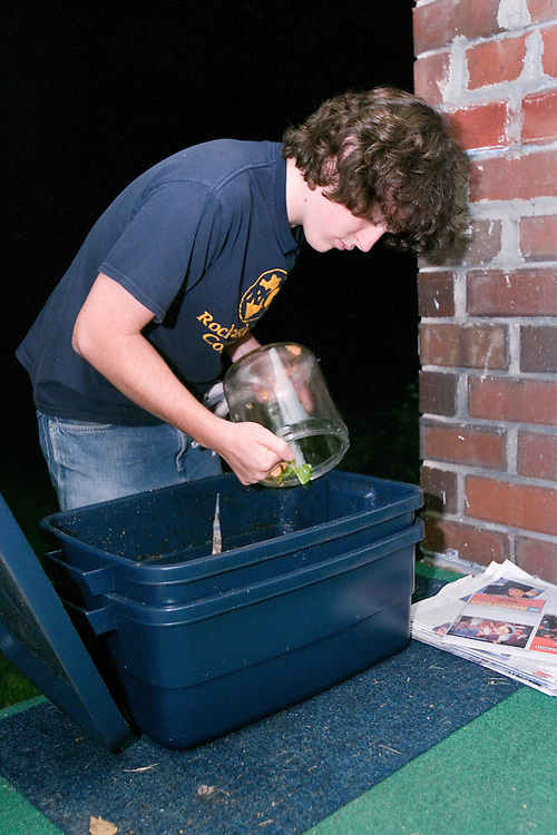 Nathan Jud, resident of Ohio University's Ecohouse, adds scraps of food leftover from dinner preparation to the compost bin at the house on Monday, 9/25/06.