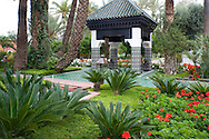 An ornately tiled pavilion surrounded by geraniums and palm trees in the garden of La Mamounia Hotel in Marrakech, Morocco
