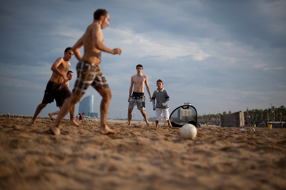 A group of people play football at the beach in Barcelona, Spain.