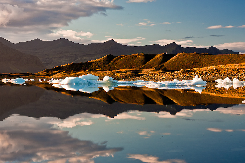 The placid waters of Jokulsarlon iceberg lagoon provide for perfect reflections or the mountains nearby.