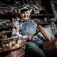 un anziano artigiano del rame nel suo laboratorio