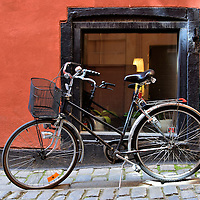 Bicycle in Old Town Alley in Stockholm, Sweden<br /> Österlånggatan Street in Gamla stan or Old Town is connected by a series of very small alleys, many of which resemble tunnels.  They are so narrow they typically only accommodate pedestrians and bicycles like this one leaning against the wall of Stora Hoparegrånd. This implies that this passageway was originally used by barrel makers.
