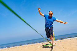 Portobello, Scotland, UK. 25 April 2020. Views of people outdoors on Saturday afternoon on the beach and promenade at Portobello, Edinburgh. Good weather has brought more people outdoors walking and cycling. Police are patrolling in vehicles but not stopping because most people seem to be observing social distancing. Rhys, a Portobello resident,  practicing his tightrope walking skills on the beach. Iain Masterton/Alamy Live News