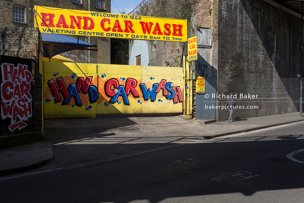 As the second week of the Coronavirus lockdown continues around the capital, and the UK death toll rising by 563 to 2,325, with 800,000 reported cases of Covid-19 worldwide, a solitary person walks past the gates of a local hand car wash and valeting business under one of the railway bridges at Loughborough Junction, closed in accordance with the government's forced closure of businesses and lockdown, on 1st April 2020, in London, England.