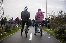 October 24, 2016 - Calais, France - Refugees arriving and waiting at the hangar of distribution of refugees with their luggage. Two bicycle refugees in Calais observe the scene, France on october 24, 2016. The dismantling of the jungle began Monday morning. Refugees come accompanied by the associations to the starting center ''C.A.O.''. Police frames the device. More than 850 press credentials were distributed. (Credit Image: © Julien Pitinome/NurPhoto via ZUMA Press)