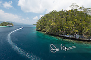 A small motorized boat navigates through the small islands that make up Raja Ampat, Indonesia.