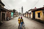 Two young vietnamese girls hangs in a gloomy street of Man Xa Village, outskirts of Hanoi, Vietnam, Southeast Asia