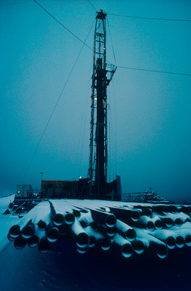 On-shore oil rig with pipes covered in winter snow.