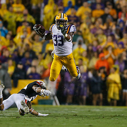 Sep 21, 2013; Baton Rouge, LA, USA; LSU Tigers running back Jeremy Hill (33) leaps over Auburn Tigers defensive back Ryan Smith (24) during a game at Tiger Stadium. Mandatory Credit: Derick E. Hingle-USA TODAY Sports