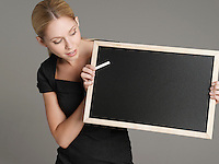 Portrait of young female teacher holding blackboard