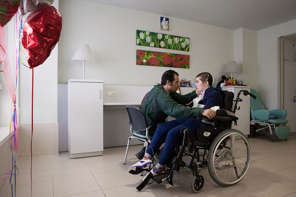 Santa Lucia Foundation, Rome, February 21, 2016. Chiara Insidioso Monda 21-year-old  and her father Maurizio, 44. 21-year-old Chiara has been hospitalized at the Santa Lucia Foundation in Rome since December 2014. In February 2014, when Chiara was only 19, she was brutally beaten by her 'partner', 16 years older than her, till she fell into a coma due to the violence of the blows. The kicks, punches and having her head slammed against a wall caused irreversible damage to Chiara's body and reduced her cerebral functioning to 10%. Chiara had to undergo three brain surgeries when she arrived at the hospital. She woke up from the coma after 10 months and is now in a state of semi-consciousness. This means that she can't talk, move or walk and has to be assisted in every single activity of daily life.<br />