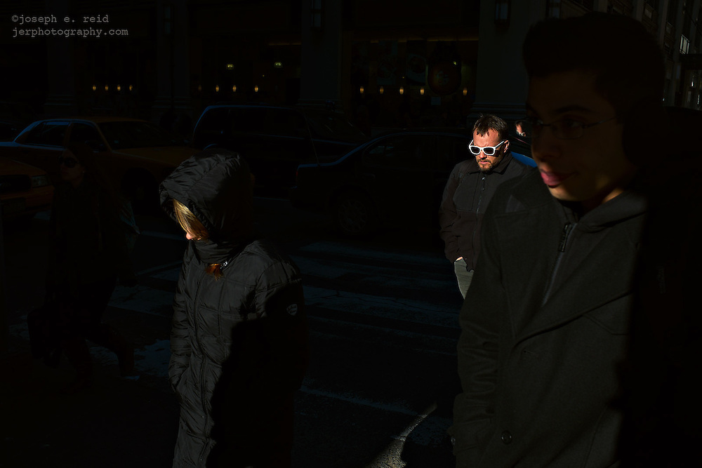 Man in white sunglasses crossing shadowy street, New York, NY, US