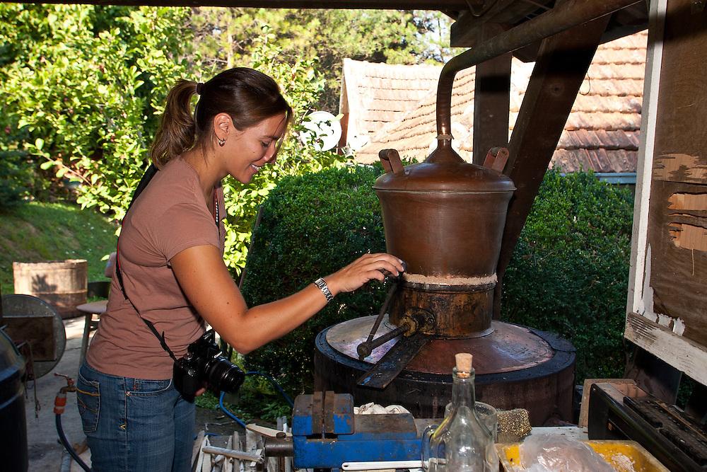 Making loza rakija (grape brandy) in Fruska Gora, Serbia. The handle on the still is periodically cranked to push the fermented grapes into the barrel.