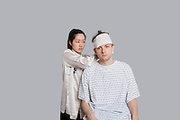 Female doctor dressing patient's head with bandage