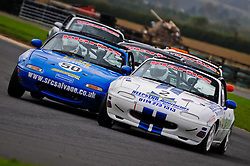 Jonathan Greensmith, car 2, holds off Luke Herbert, car 50, and a swarm of other MX-5s at Croft Circuit