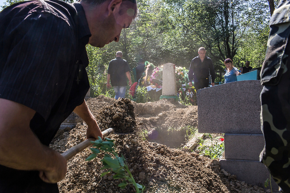 HORLIVKA, UKRAINE - MAY 24: Men shovel dirt to fill the grave of  Aleksandr Politov, a pro-Russia militia fighter who was killed when his group attacked a Ukrainian military checkpoint two days earlier in the village of Blahodatne, on May 24, 2014 in Horlivka, Ukraine. Presidential elections are scheduled for tomorrow, but pro-Russia militias have been seeking to prevent them from being administered throughout the eastern part of the country. (Photo by Brendan Hoffman/Getty Images) *** Local Caption ***