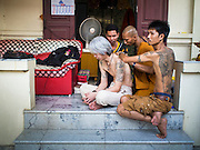"""07 MARCH 2015 - NAKHON CHAI SI, NAKHON PATHOM, THAILAND:  A man gets a """"sak yant"""" tattoo at the Wat Bang Phra tattoo festival. Wat Bang Phra is the best known """"Sak Yant"""" tattoo temple in Thailand. It's located in Nakhon Pathom province, about 40 miles from Bangkok. The tattoos are given with hollow stainless steel needles and are thought to possess magical powers of protection. The tattoos, which are given by Buddhist monks, are popular with soldiers, policeman and gangsters, people who generally live in harm's way. The tattoo must be activated to remain powerful and the annual Wai Khru Ceremony (tattoo festival) at the temple draws thousands of devotees who come to the temple to activate or renew the tattoos. People go into trance like states and then assume the personality of their tattoo, so people with tiger tattoos assume the personality of a tiger, people with monkey tattoos take on the personality of a monkey and so on. In recent years the tattoo festival has become popular with tourists who make the trip to Nakorn Pathom province to see a side of """"exotic"""" Thailand.  PHOTO BY JACK KURTZ"""