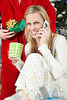 Woman in pyjamas on cell phone in front of man holding Christmas present