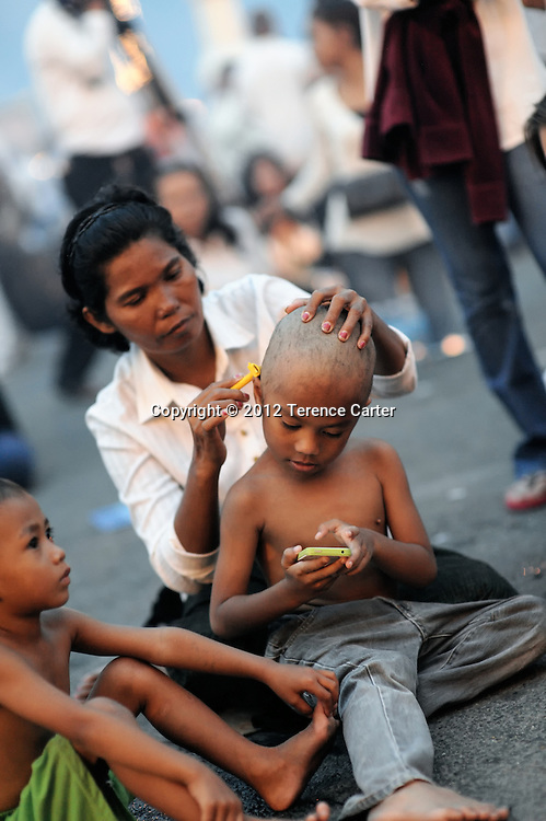 A young boy has his head shaved as a sign of respect for the passing of King Father Norodom Sihanouk, whose body was returned to the Royal Palace, Phnom Penh, starting a week of mourning in Cambodia.