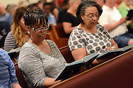 Deaconess Norma Teat (left) and Dennise Veasley (right) sing a hym at Bethlehem AME Church during an Interfaith Prayer Service for peace, racial justice and reconciliation Tuesday June 23, 2015 in Langhorne, Pennsylvania. (Photo by William Thomas Cain)