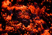 Embers from a fire glow with heat.