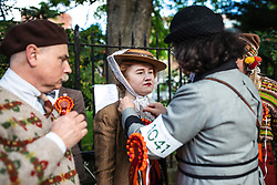 © Licensed to London News Pictures. 04/05/2019. London, UK. A woman has her bonnet fixed at the start of the annual Tweed Run bicycle ride, in which participants cycle around the capital wearing vintage tweed outfits. Photo credit: Rob Pinney/LNP