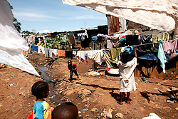 Sunkari's children hang their washing over the drain they live next to in Kroo bay slum. ..Kroo Bay, Freetown, Sierra Leone.