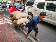05 OCTOBER 2012 - BANGKOK, THAILAND:  Men push a handtruck of rice from a warehouse to a business in the Chinatown section of Bangkok, Thailand. Thailand is one of the leading rice producers in the world.      PHOTO BY JACK KURTZ