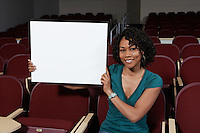 Female student holding blank board in lecture theatre, portrait
