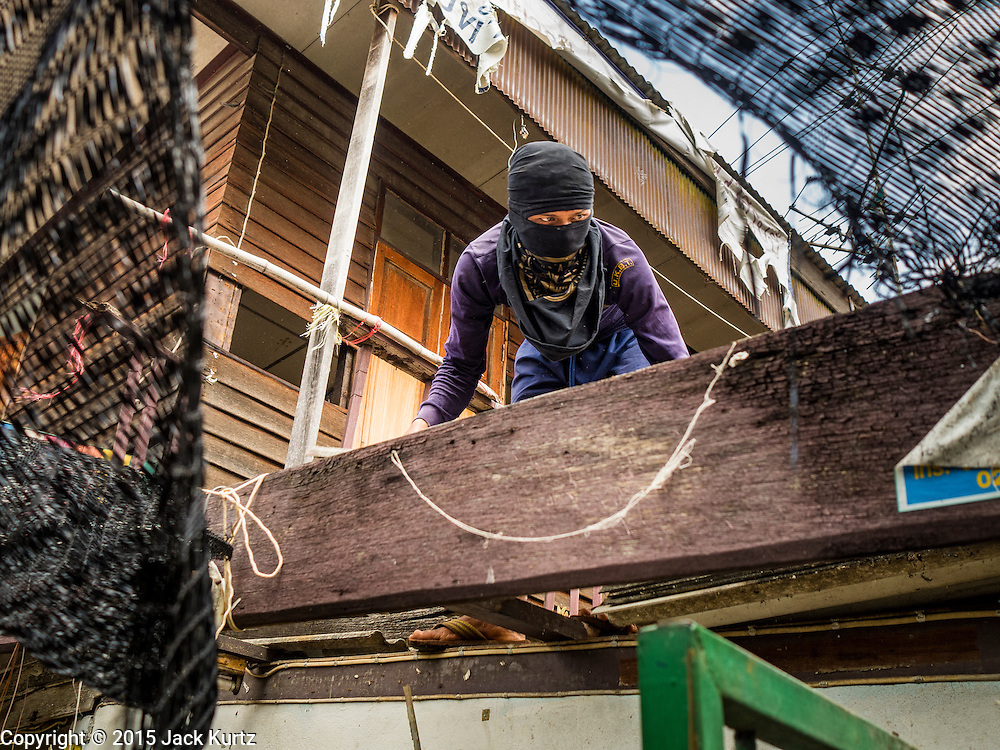 16 OCTOBER 2015 - BANGKOK, THAILAND: A demolition worker starts dismantling the roof of a home in the Wat Kalayanamit neighborhood. The owner was evicted from the house minutes earlier. Fifty-four homes around Wat Kalayanamit, a historic Buddhist temple on the Chao Phraya River in the Thonburi section of Bangkok, are being razed and the residents evicted to make way for new development at the temple. The abbot of the temple said he was evicting the residents, who have lived on the temple grounds for generations, because their homes are unsafe and because he wants to improve the temple grounds. The evictions are a part of a Bangkok trend, especially along the Chao Phraya River and BTS light rail lines. Low income people are being evicted from their long time homes to make way for urban renewal.    PHOTO BY JACK KURTZ