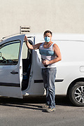 man holding bottle for disinfecting his hands before getting in the car during the Covid 19 crisis and lockdown France Limoux May 2020