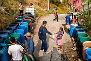 Ecatapec residents wait for their family's barrels to be filled, and then sign a waiver to indicate how much they have received. Though the water is supposed to be free of charge, residents are often required to pay a mandatory 'tip' for the tanker crew or face the possibility that the trucks will not return the following week.
