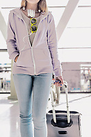 Portrait of young teenage girl walking with her suitcase in airport