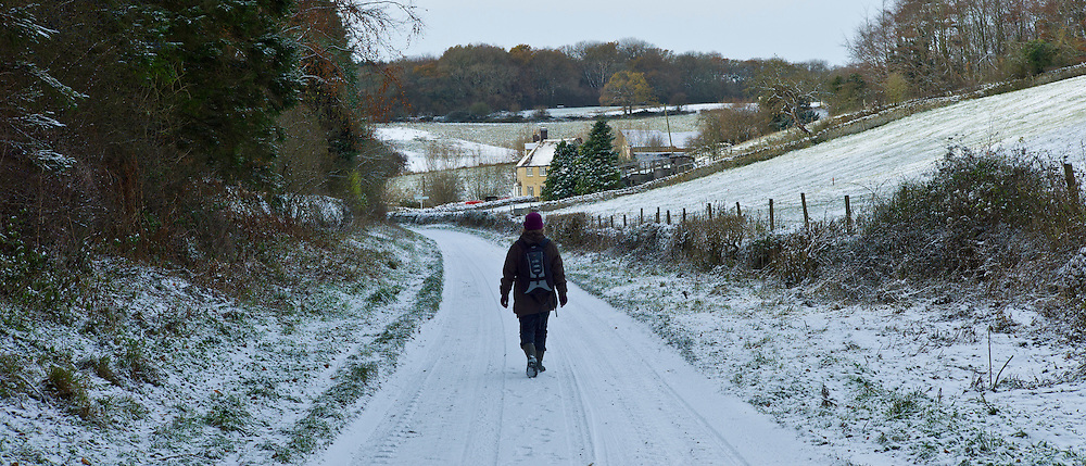 Walker in country lane in frosty wintry landscape in The Cotswolds, Oxfordshire, UK
