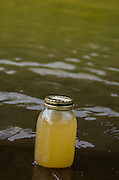 A glass jar filled with polluted water shows the discoloration caused by the sediment which has polluted the Animas River following the King Gold Mine spill.