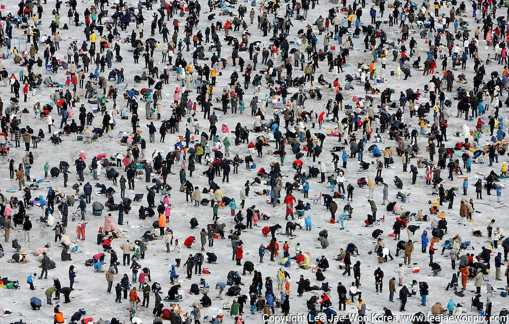 People drop lines in holes on a frozen river at an event to fish trout in Hwacheon, about 20 km (12 miles) south of the demilitarised zone separating two Koreas, northeast of Seoul January 13, 2008. More than 1,000,000 people attend at the annual ice festival which lasts for three weeks in January. /Lee Jae-Won