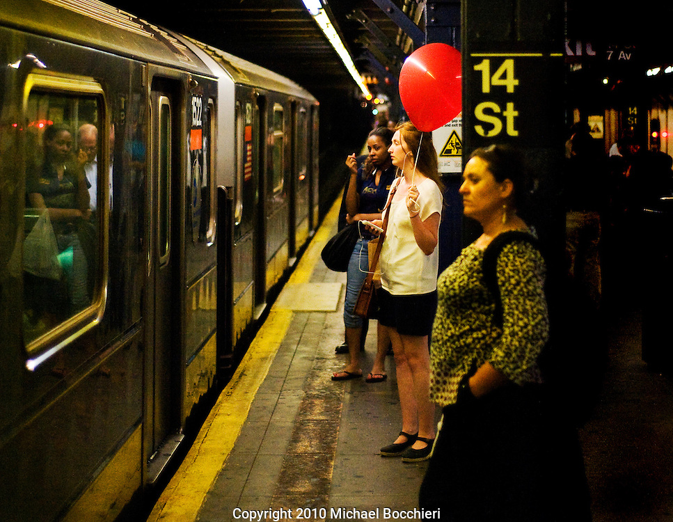 NEW YORK, NY - June 16:  A girl stands on the 14th Street subway platform with a large red balloon in Manhattan on June 16, 2010 in NEW YORK, NY.  (Photo by Michael Bocchieri/Bocchieri Archive)