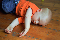 Young boy lying on wooden floor,